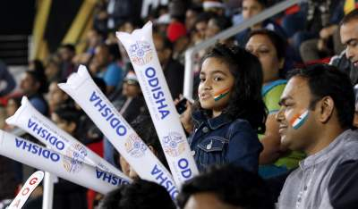 young hockey fan in stadium holding dummy hockey sticks
